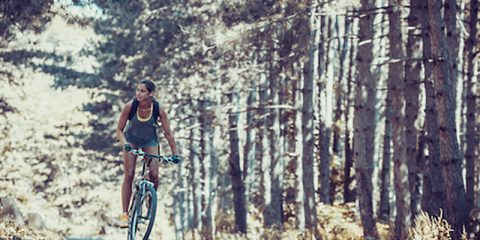 Woman riding a mountain bike in the forest.Grain effect added.